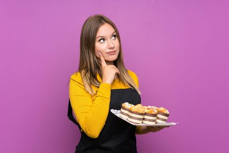 Photo pour Teenager girl holding lots of different mini cakes over isolated purple background thinking an idea - image libre de droit
