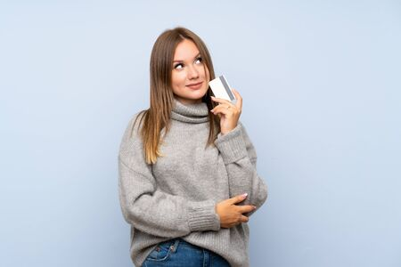 Photo pour Teenager girl with sweater over isolated blue background holding a credit card - image libre de droit