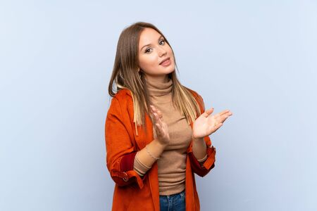 Photo pour Teenager girl with coat over isolated blue background applauding after presentation in a conference - image libre de droit