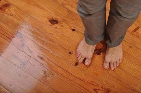young man bare feet on wooden floor background