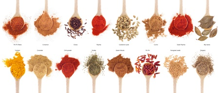 gorgeous collection of 16 spices on wooden spoons (cumin, coriander, cloves, curry, chili, piri piri, cinnamon, cardamom, fenugreek,  garam masala, oregano, parsley, paprika, turmeric, bay) isolated on white background