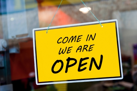 come in we are open sign hanging on a window door outside a restaurant, store, office or other