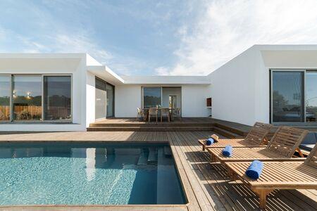 Foto de Wooden lounge chairs in modern villa pool and deck - Imagen libre de derechos