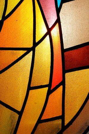 Foto de Close-up shot of varicoloured stained glass window backlit by the sun - Imagen libre de derechos