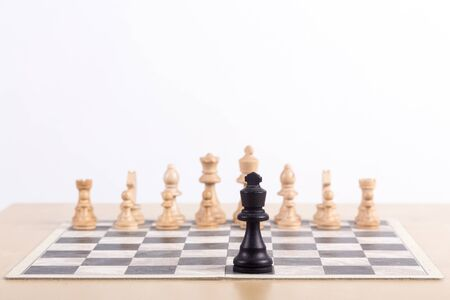 Foto de Close up of chess board with all the white pieces at start position and black king standing alone  - Imagen libre de derechos