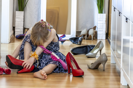 Photo pour Little girl wearing big high-heeled mothers shoes - image libre de droit