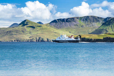 Photo pour Calmac ferry on the sea with green mountains in the background - Caledonian MacBrayne ferry operating in Highlands of Scotland, Outer Hebrides - image libre de droit