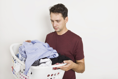 Photo pour Frustrated young man holding basket full of clothes. Laundry time - image libre de droit