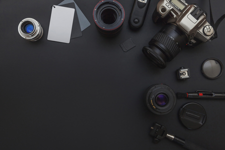 Foto de Photographer workplace with dslr camera system, camera cleaning kit, lens and camera accessory on dark black table background. Hobby travel photography concept. Flat lay top view copy space - Imagen libre de derechos