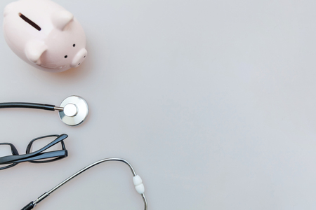 Photo pour Medicine doctor equipment stethoscope or phonendoscope piggy bank glasses isolated on white background. Health care financial checkup or saving for medical insurance costs concept - image libre de droit