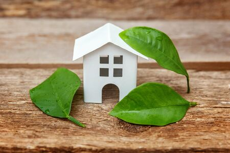Photo pour Miniature white toy model house with green leaves on wooden backgdrop. Eco Village, abstract environmental background. Real estate mortgage property insurance dream home ecology concept - image libre de droit