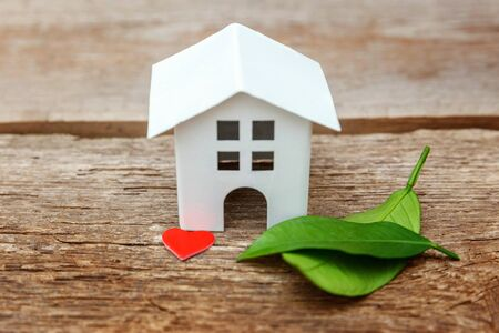 Photo pour Miniature white toy model house with green leaves and red hearts on wooden backgdrop. Eco Village, abstract environmental background. Real estate mortgage property insurance dream home ecology concept - image libre de droit
