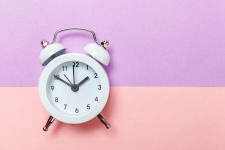Foto de Ringing twin bell vintage classic alarm clock Isolated on purple pink pastel colourful background. Rest hours time of life good morning night wake up awake concept. Flat lay top view copy space - Imagen libre de derechos