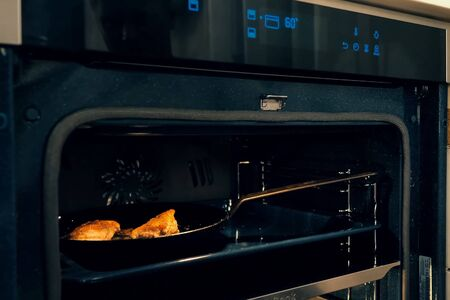 Photo pour Meat is roasted in the oven. Electric Oven by the stove. - image libre de droit