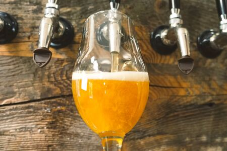 Foto de Pouring beer into a glass from the tap at the bar. Beer bottling. - Imagen libre de derechos