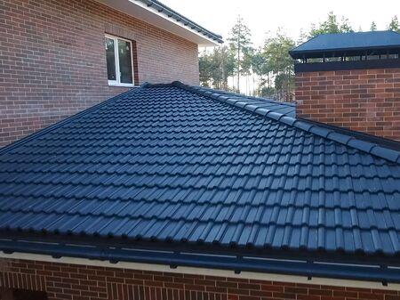 Photo pour House with a ceramic tile roof. cement-sand roof tiles. - image libre de droit