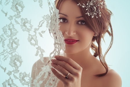 Portrait of a beautiful bride smiling behind her veil.