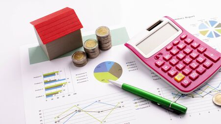 Photo pour Mortgage loans concept with red house and coin stack, calculator and pen on business report backgrounds - image libre de droit