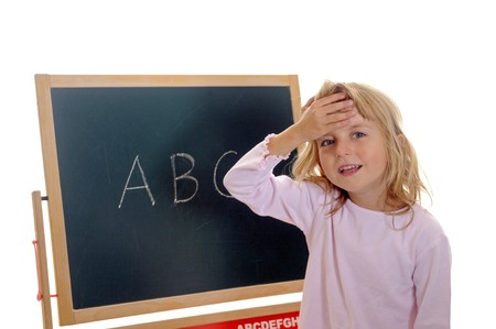 little girl in front of board with ABC