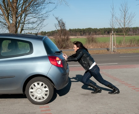 annoyed young woman pushes her car