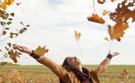 cheerful young woman throws with leaves