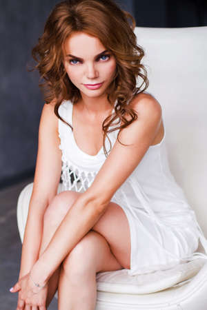 Photo pour Portrait of the woman in the white dress, sitting on the chair. - image libre de droit