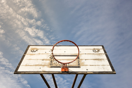 Old street basketball basket with a cloudy blue sky