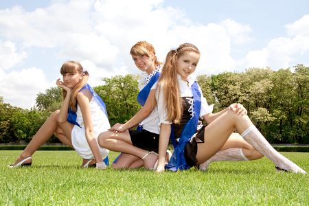 three funny graduates posing outdoors