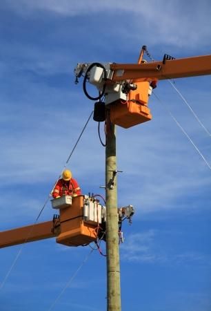 Photo pour Two electrical technicians connecting power to a new construction  - image libre de droit