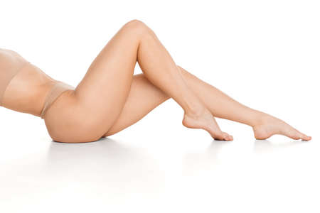 Photo for Beautiful slender tanned female legs in underwear over white background. - Royalty Free Image