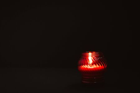 Photo pour White burning candle in red glass on black background. Mourning, burning candle. Mourning, sadness, sorrow concept. Copy space - image libre de droit