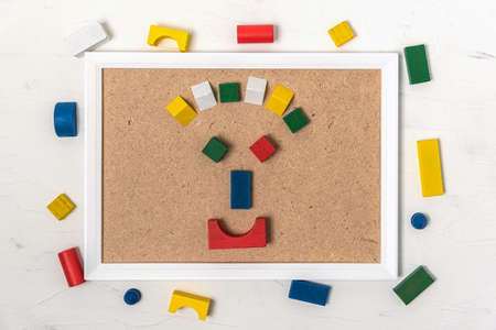 Anthropomorphic face from colorful wooden blocks n frame on white wooden background, top view with copy space.