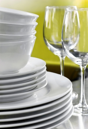White commercial plates, bowls and blurred wine glasses on green background