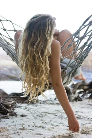 Blond girl lying in hammock on the beach