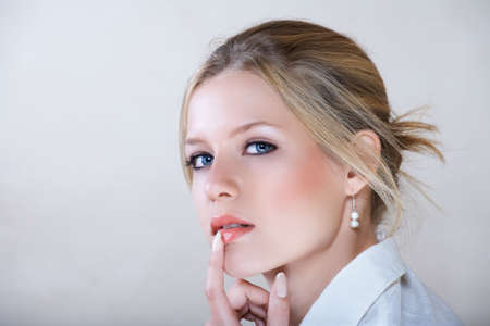 Young beautiful businesswoman with blond hair and blue eyes in white shirt holding her finger on the lips