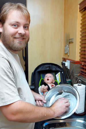 young man washing the dishes with a smile while a baby boy keeps him company in a chair.