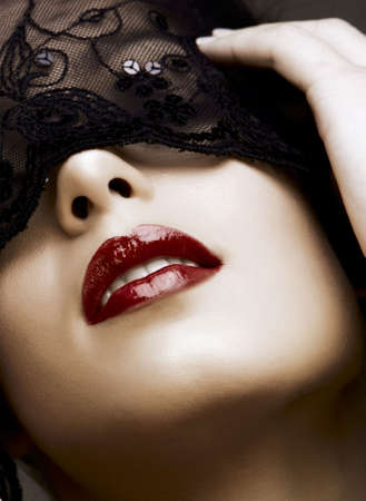beautiful woman with red lips and lace mask over her eyes.