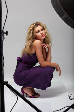 beautiful professional female model in purple dress resting between shots in a photographic studio shoot set-up