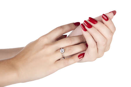 closeup hands of young woman with red manicure polished nails wearing an expensive engagement ring with a diamond