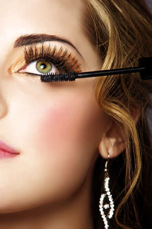 portrait of beautiful woman with smoky gold eyeshadow and long false eyelashes applying mascara with a wandの写真素材