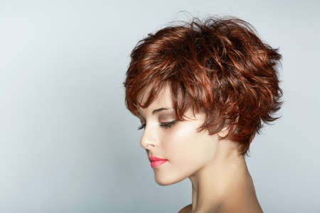 beautiful young woman with short brown haircut wears pink lipstick on studio background with copy space