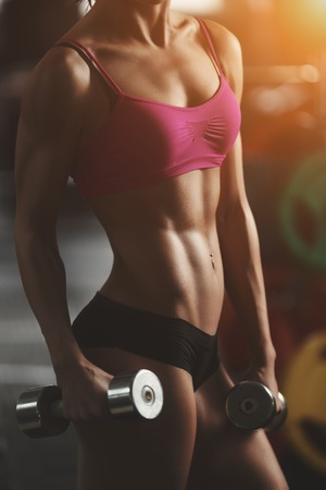 Foto de Brutal athletic woman pumping up muscles with dumbbells. Brunette sexy fitness girl in pink sport wear with perfect body in the gym posing before training set. Attractive fitness woman - Imagen libre de derechos