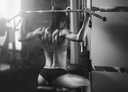Foto de Black and white photo of a strong woman from behind. Brunette sexy fitness girl in sport wear with perfect body in the gym posing before training set. Attractive fitness woman, trained female body - Imagen libre de derechos