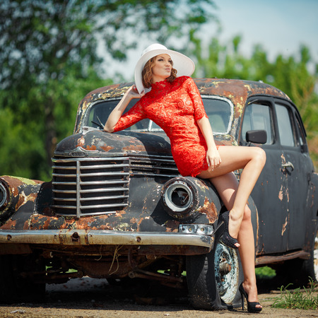 Beautiful young woman looks sexy, comes against the backdrop of an old black car in a red dress. Girl in red dress holding a white hat. Image of a woman who looks away.