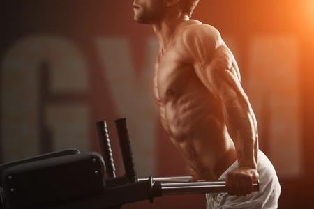 Foto de Strong muscular bodybuilder doing exercise on bars in the gym - Imagen libre de derechos