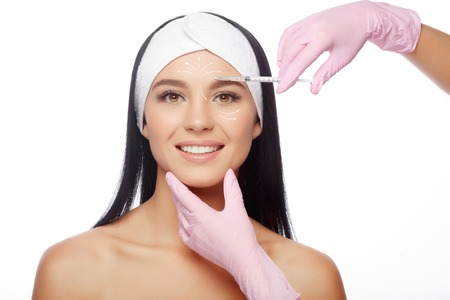 Photo pour Beautiful woman getting lifting injection in forehead. Close-up woman hyaluronic acid injection. Injections of skin rejuvenation. Cosmetic procedures, injections, hyaluronic acid. - image libre de droit