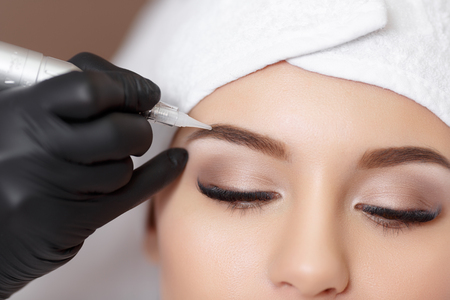 Foto de Permanent makeup. Permanent tattooing of eyebrows. Cosmetologist applying permanent make up on eyebrows- eyebrow tattoo - Imagen libre de derechos