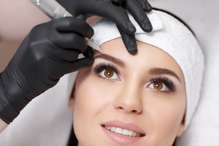 Permanent makeup. Permanent tattooing of eyebrows. Cosmetologist applying permanent make up on eyebrows- eyebrow tattooの写真素材