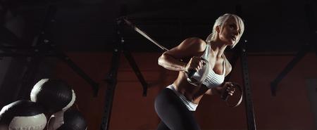 Photo pour Fitness woman workout on the TRX in the gym - image libre de droit