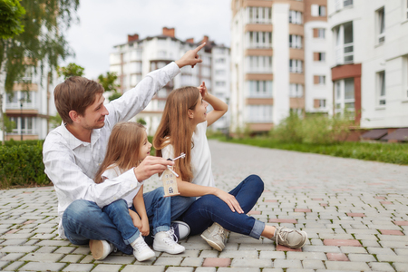 Photo for Happy family in front of new apartment building - Royalty Free Image